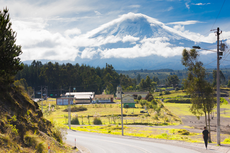 Cotopaxi Ecuador May 2018 a person walks at sunrise along the road leading to the national park and in the background the snow capped volcano Editorial