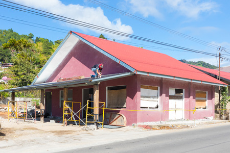 Boquete Panama December 16, 2018 renovations are taking place throughout the city. This worker is painting the roof of this building