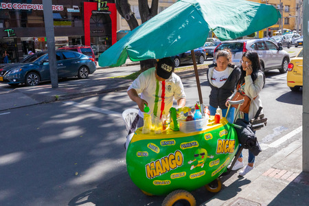 Bogota,  Colombia  July 7 In Bogota street vendors are common and locals are used to eat a snack  as they walk. Shoot on July 7, 2019