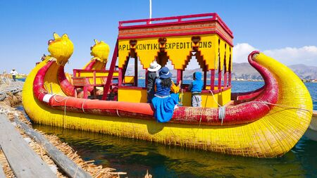 Lake Titicaca, Peru, August 16 a typical boat made of straw that takes tourists to visit the islands of Lake Titicaca departs from the pier. Shoot on August 16, 2019 Reklamní fotografie
