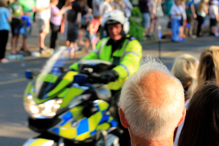 Back of an healthy looking elderly man with white thinning hair and balding sun tanned head. Also a policeman on a motorbike rides past and both look at each other, as if bald man has been caught