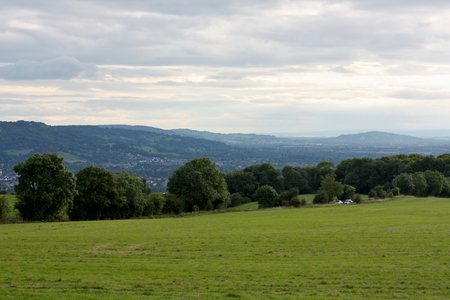 gloucestershire: Beautiful English rural country landscape with green fields, row of trees, hills and clouds.  The location is the Cotswolds, Cheltenham, Gloucestershire Stock Photo