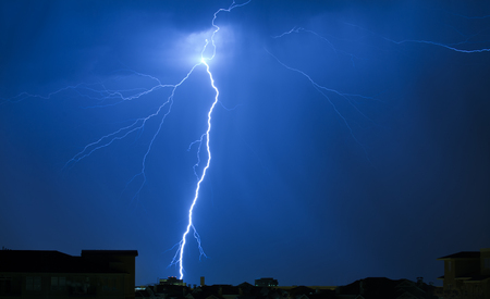 streak lightning: Lightning Strike on a Dark Blue Sky Hitting Building in Distance