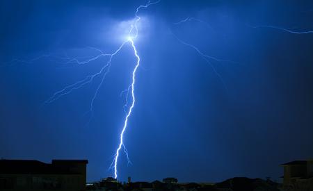 black blue: Lightning Strike on a Dark Blue Sky Hitting Building in Distance