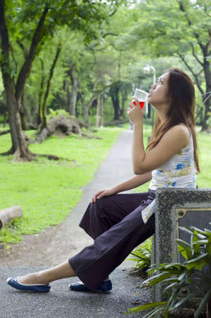 Beautiful woman about to drink a cup of red drinks while waiting along a long path to the woods photo
