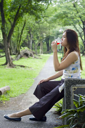 Beautiful woman waiting on a path while drinking a cup of red drink photo