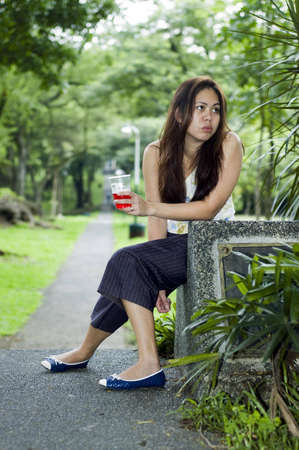 A tired and negative looking woman waiting along a long path while holding a cup of red drink  on her hand photo