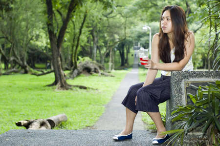 A tired looking woman waiting along a long path while holding a cup of red drink  on her hand photo