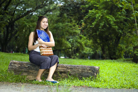 capri pants: Asian woman showing off her blue chinese wooden fan with lush foilage at the background.