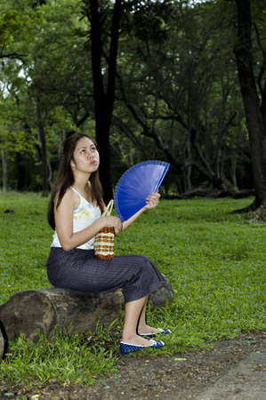 capri pants: Part of series. Asian Woman sitting on a log bench  with woods at the background.  Woman is cooling herself down with a wooden fan.