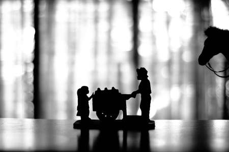 ice cream cart: Silhouette of a figurine of an ice cream cart vendor selling to two kids with a horse on the background