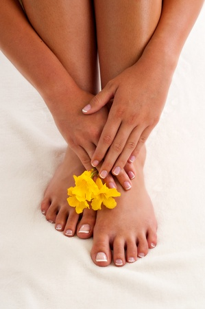 French manicured hands positioned above her french pedicured feet.  There is also 3 yellow flowers pictured.
