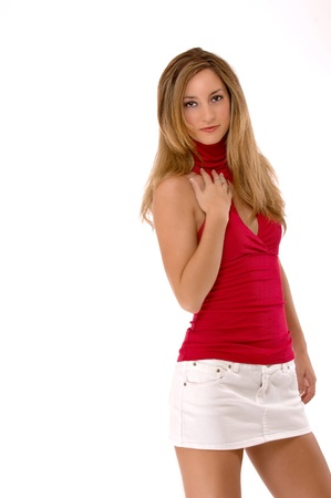 Young blond woman with one hand on her chest.  She is wearing a red sleeveless shirt and white mini skirt.  Studio shot, isolated on a white background.