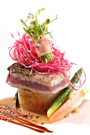 ahi: Seared ahi tuna, beet slaw & ginger wrapped sprouts served over rice with a ginger sauce on a white plate Stock Photo