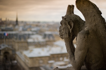 ile de la cite: Stone gargoyle with horns, perched on a corner of the cathedral of Notre Dame, peering over the city of Paris.  Stock Photo