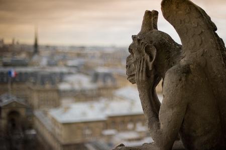 """Stone waterspuwer met hoorns, zat op een hoek van de kathedraal van Notre-Dame, """"peering"""" over de stad Parijs.  Stockfoto"""