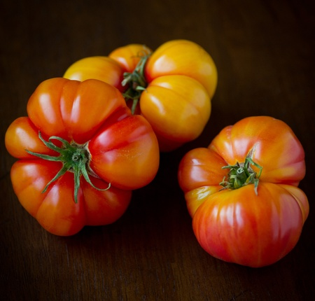 3 Large, ripe heirloom tomatoes shot on a wood background. Stock Photo