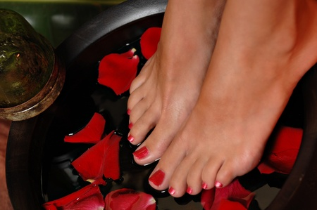 Close-up van de voeten van een vrouw op een roos pedaal bad, Stockfoto