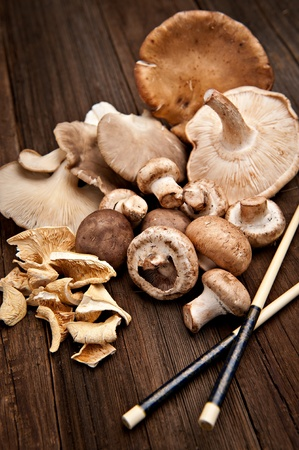 Variety of various mushrooms shot on a natural wood background in select focus.  Chopsticks are also featured in this image.
