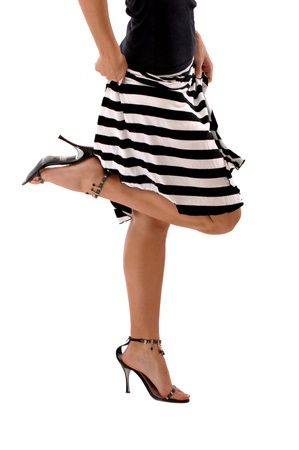 Woman wearing a black and white striped skirt and black high heals with 1 Leg-Up.