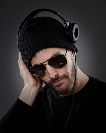 DJ listening to headphones on a dark background. photo