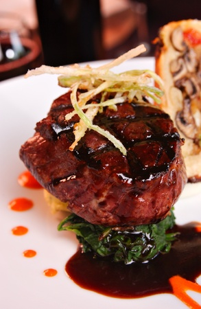 Grilled filet Mignon over mashed potatoes & spinach, topped with .  Roasted garlic cloves are also displayed.