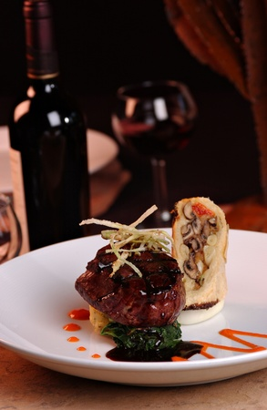 Grilled filet Mignon over mashed potatoes & spinach, topped with .  Red wine and roasted garlic cloves are also displayed.