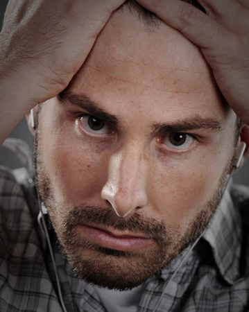 ear buds: Young man holding his hands on his head in frustration.  He also has white ear buds in for listening to music. Stock Photo