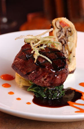 Grilled filet Mignon over mashed potatoes & spinach, topped with .  Roasted garlic cloves are also displayed. photo