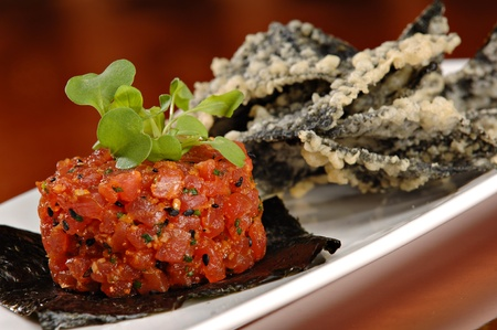 Raw ahi tuna tartare appetizer atop a sheet of nori and garnished with fresh green sprouts. Served with a side of tempura tortilla chips. photo