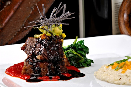 Stacked braised short ribs on a bright red tomato paste sauce.  Garnished with avocado, sliced tortilla chips and a red wine reduction sauce.  Colorful sauteed spinach is displayed behind the meat and polenta to the side. Stock Photo
