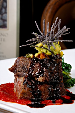 Stacked braised short ribs on a bright red tomato paste sauce.  Garnished with avocado, sliced tortilla chips and a red wine reduction sauce.  Colorful sauteed spinach is displayed behind the meat.