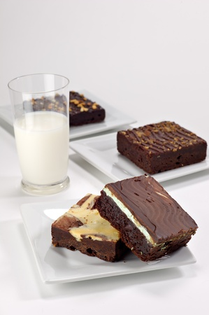 brownie: Chocolate mint brownie square stacked on top of a cream cheese brownie square shot in the studio on a white plate with a glass of milk in the background.  There are 2 plated brownies in the background as well. Stock Photo