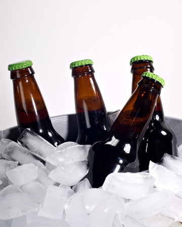Four brown beer bottles on ice with bright green caps shot on white.
