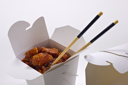 Orange chicken in a white takeout container and chopsticks, isolated on white.  There is also an empty take out container to the side.