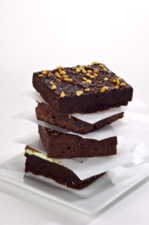 Four beautifully stacked gourmet brownies stacked on a white plate with parchment paper between each brownie.