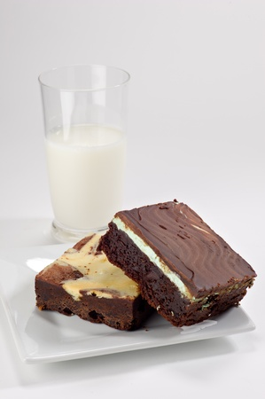 chocolate mint: Chocolate mint brownie square stacked on top of a cream cheese brownie square shot in the studio on a white plate with a glass of milk in the background.