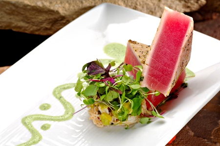 Seared ahi tuna fillets creatively stacked next to a side rice garnished with colorful sprouts.  A green trail of wasabi sauce completes the plate.