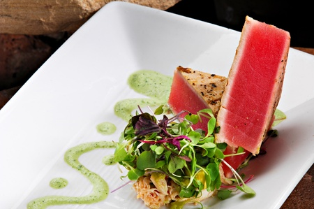Aangebraden Ahi tonijn filets creatief gestapeld naast een kant rijst gegarneerd met kleurrijke spruiten. Een groene spoor van wasabi saus maakt de plaat.