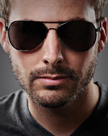 어두운 선글라스를 착용하는 매력적인 젊은 남자의 초상화.