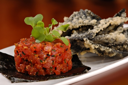 Raw ahi tuna tartare appetizer atop a sheet of nori and garnished with fresh green sprouts. Served with a side of tempura tortilla chips.