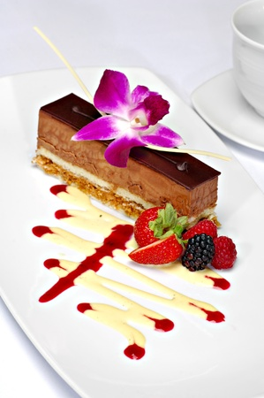 Beautifully plated chocolate mousse cake garnished with a purple orchid, strawberry, backberry and raspberry.  A zig zag of white chocolate and strawberry sauce completes the plate. Imagens