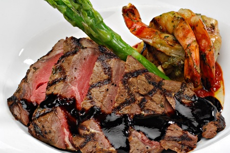 Sliced steak topped with a red wine reduction sauce, plated alongside fresh green asparagus spears and prawns. Banco de Imagens - 10536978