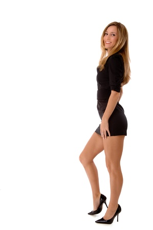 Full body profile of a young blond woman smiling.  She is wearing a tight, short, black dress and high heel shoes.  Studio shot, isolated on a white background.