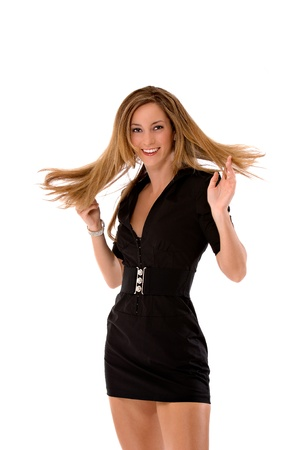 Young blond woman twirling with her hands in her hair and her hair is twirling about.  She is wearing a tight, short, black dress.  Studio shot, isolated on a white background. Stock Photo
