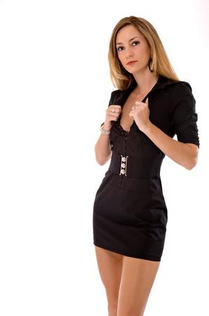 minifalda: Mujer rubia joven que sostiene la parte delantera de su vestido con ambas manos. Ella está usando un apretado, vestido corto, negro. Estudio de disparo, aislado en un fondo blanco.