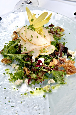 Beautifully plated fresh mixed green salad with pears, walnuts and goat cheese.  This salad is served on a glass plate. Stock Photo