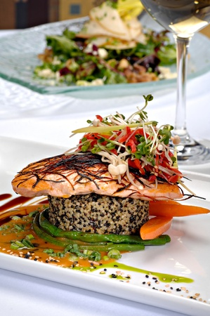 plated: Beautifully plated salmon fillet garnished with colorful green sprouts &  red peppers.  All on top of black and brown rice with asparagus and carrots.