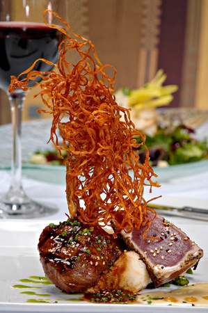 Grilled lamp chop topped with a light sauce and green onions, plated alongside seared ahi tuna over mashed potatoes.  All is topped with deep fried shredded sweet potatoes. Stock Photo - 10629001