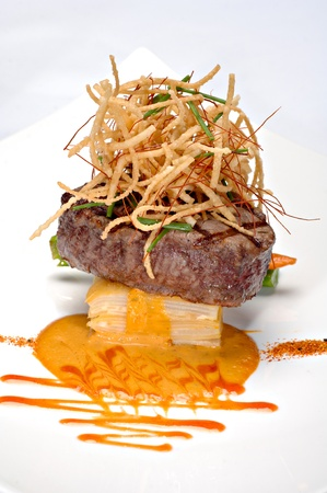 Grilled Filet Mignon over scalloped potatoes au gratin, topped with deep fried onions.  photo